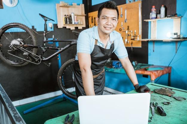Meccanico di bicicletta in grembiule con i guanti che sorride mentre si trova vicino al laptop