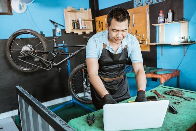 Meccanico di bicicletta in grembiule che indossa guanti utilizzando laptop per cercare pezzi di ricambio