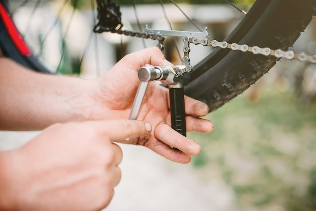 Le mani del meccanico della bicicletta regolano la catena della bicicletta con strumenti di servizio.