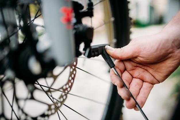 Le mani del meccanico della bicicletta regolano i freni a disco. ciclo officina all'aperto. lo sport in bicicletta, l'uomo di servizio barbuto lavora con la ruota