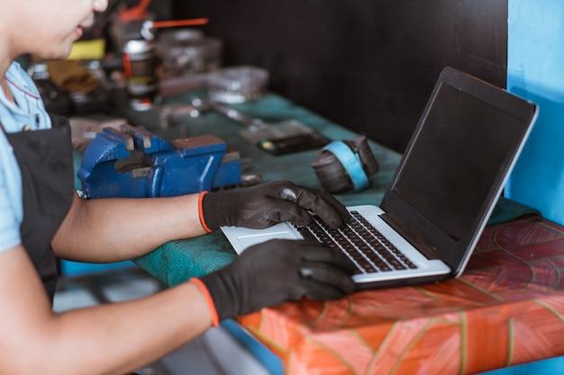 Un meccanico di biciclette che indossa guanti utilizza un computer portatile durante la navigazione