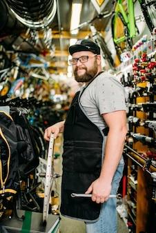 Meccanico di biciclette con ruota nel negozio di biciclette