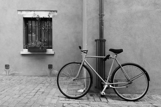 Bicicletta parcheggiata in strada a rimini, italia. fotografia urbana in bianco e nero