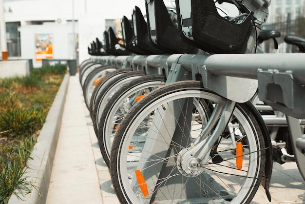 Parcheggio biciclette in affitto. punto noleggio di mezzi pubblici comunali per passeggiate attive nel parco o in città. primo piano di ruote di bicicletta in fila. messa a fuoco selettiva.