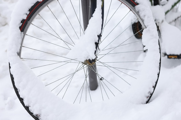 La ruota della bicicletta è ricoperta di neve sul concetto di deposito di biciclette su strada