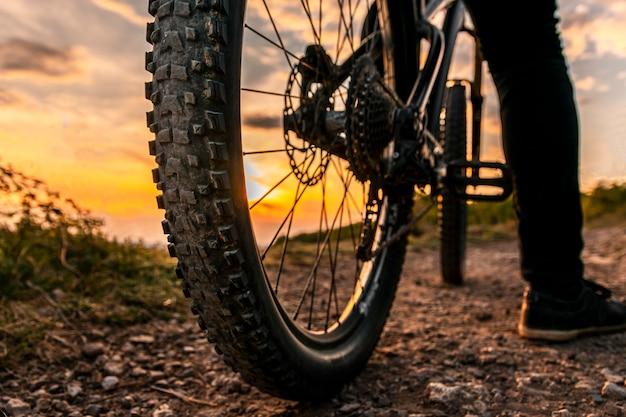 Le ruote di bicicletta si chiudono sull'immagine sul tramonto