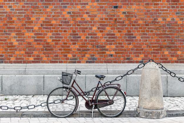 Bicicletta con cesto vicino al muro di mattoni rossi. concetto di stile di vita ecologico e urbano per il trasporto nella città vecchia