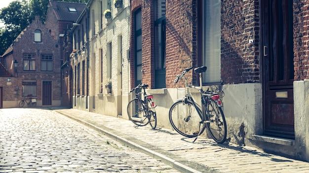 Biciclette alla vecchia facciata della costruzione sulla via accogliente, vecchia città europea provinciale.