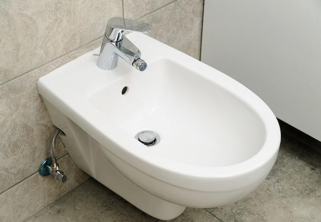 Bidet con rubinetto dell'acqua fissato a parete.