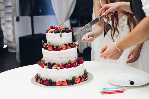 Grande incredibile torta nuziale gustosa con panna montata bianca ricoperta da bacche fresche e succose e frutta piena. bella pasticceria a strati da forno che serve sul tavolo in un ristorante di lusso luxury