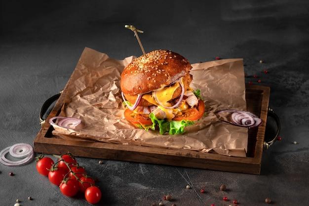 Grande hamburger americano su sfondo nero. cotoletta con formaggio, pomodoro, cipolla e insalata su un vassoio di legno, vista laterale