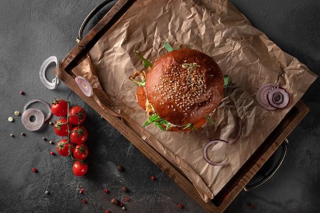 Grande hamburger di pollo al curry americano su sfondo nero. cotoletta con formaggio, pomodoro, cipolla e rucola su un vassoio di legno, vista dall'alto