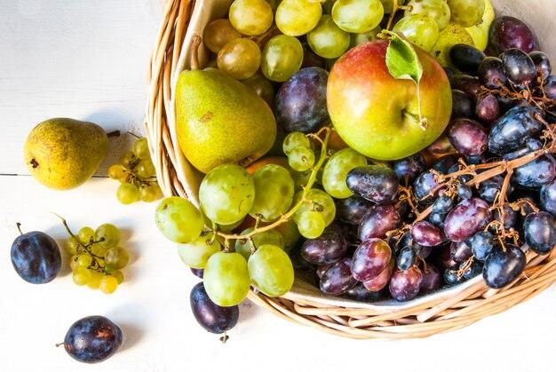Grande cesto con frutta autunnale sul tavolo di legno bianco