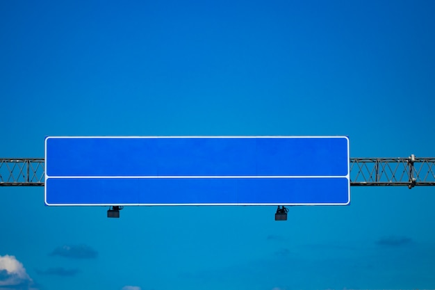 Segnale stradale grande autostrada vuota con cielo blu sfumato.