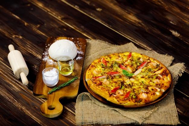 Grande ciotola di pizza calda e gustosa di pesce pronta per essere servita come cibo tradizionale italiano messo su tovaglia classica su tavola di legno marrone decorata da ingredienti di farina, pasta, olio e mattarello