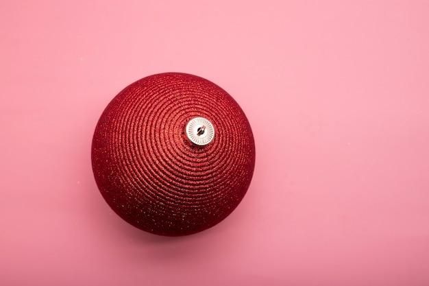 Grande palla di natale rosso brillante su sfondo rosa