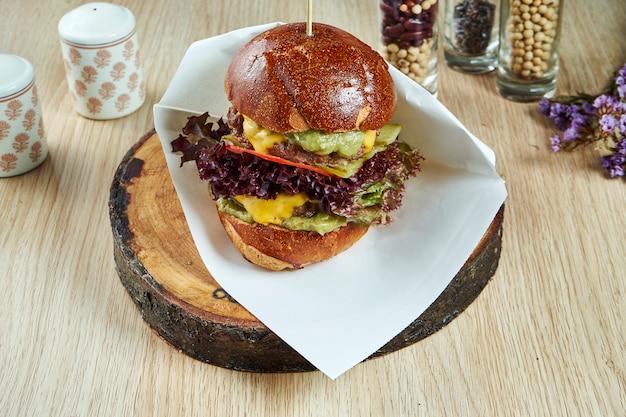 Grande hamburger con carne, formaggio, cipolle, guacamole su un tavolo di legno. gustoso cibo da strada. visualizza