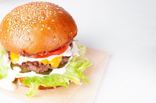 Grande cheeseburger con pomodoro, formaggio cheddar e lattuga. messa a fuoco selettiva. spase per un testo. isolato su uno sfondo bianco.