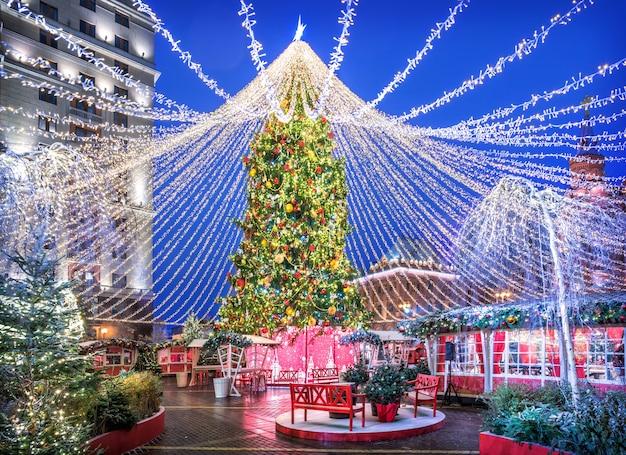 Grande albero di natale in piazza manezhnaya a mosca, panchine e case alla luce delle luci notturne festive