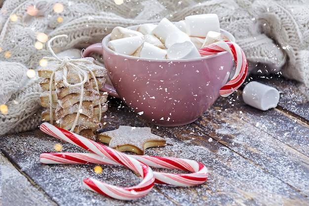 Grande tazza di cappuccino con marshmallow, bastoncini di zucchero e biscotti sulla tavola di legno marrone con luci di natale.