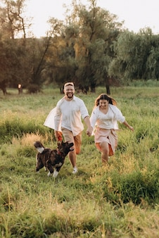 Grande cane a passeggio con un ragazzo e una ragazza nella prateria verde