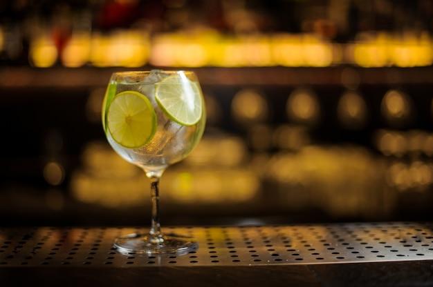 Bicchiere da cocktail grande ed elegante con cocktail fresco aspro e dolce con fette di lime
