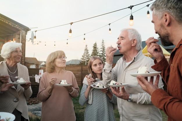 Grande famiglia in piedi nel cerchio e mangiare la torta insieme durante la festa all'aria aperta