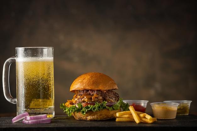 Grande hamburger fresco con birra e condimento, cibo spazzatura