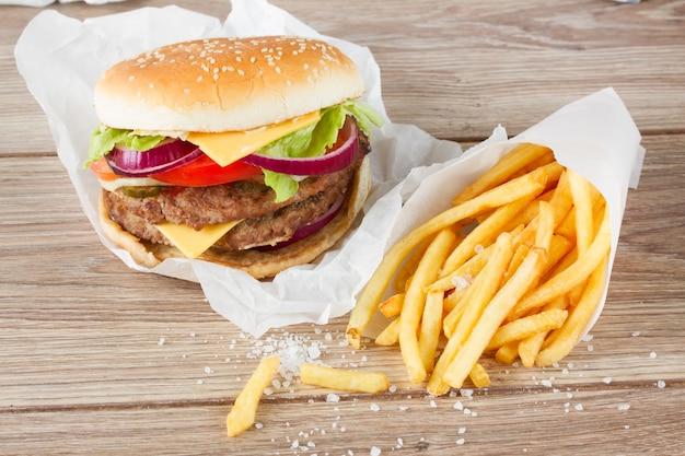 Grande hamburger fresco con patatine fritte sulla tavola di legno