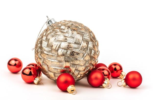 Grande palla dorata di natale e piccole palline rosse su un bianco isolato.