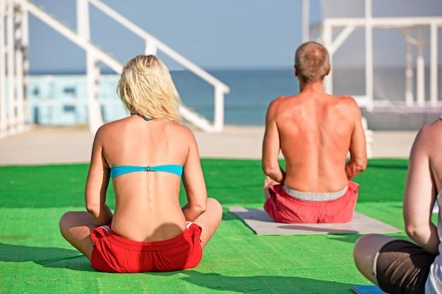 Grande gruppo di adulti che frequentano una lezione di yoga fuori sulla spiaggia