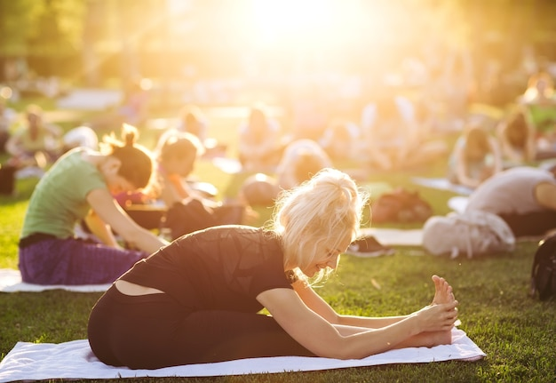 Grande gruppo di adulti che frequentano una lezione di yoga fuori nel parco