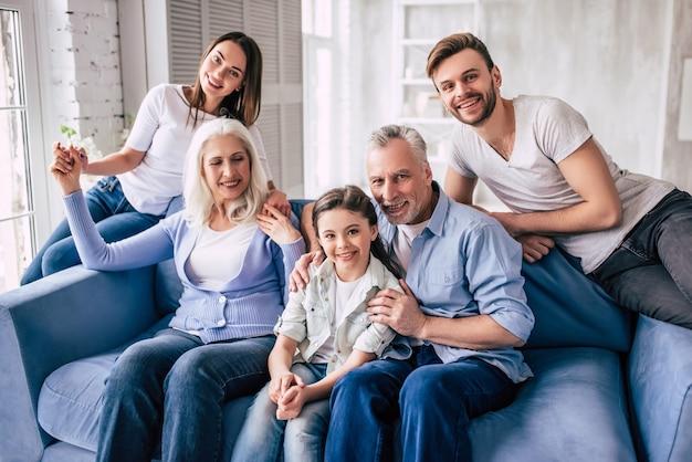 La grande famiglia felice seduta sul divano
