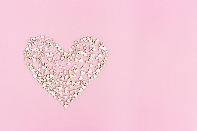 Il grande cuore è costituito da tanti piccoli cuori su sfondo rosa con copia spazio per testo o congratulazioni. concetto di amore o vacanze.