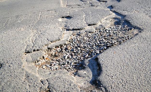 Grande buco nel primo piano della strada asfaltata