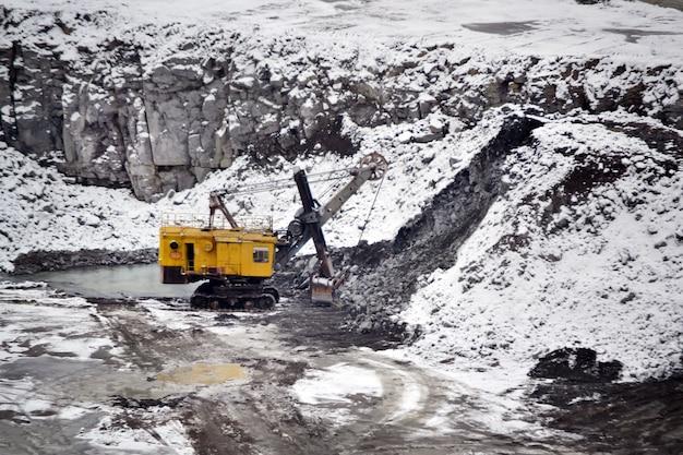 Grande escavatore giallo enorme nell'inverno della cava di granito