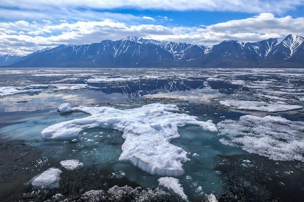 Grande lastrone di ghiaccio con fondotinta subacqueo blu, paesaggio primaverile