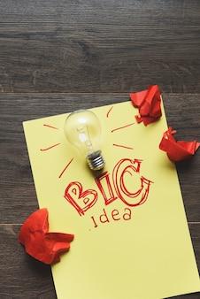 Grande idea con lampadina e carta stropicciata rossa