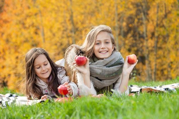 Grandi e piccole sorelle si trovano, giocano con mele rosse su sfondo di erba verde di alberi d'oro della foresta d'autunno
