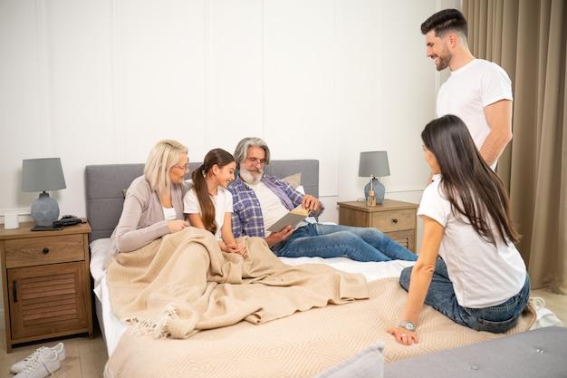 Grande padre di famiglia multigenerazionale madre e nonni anziani che leggono un libro con la nipote