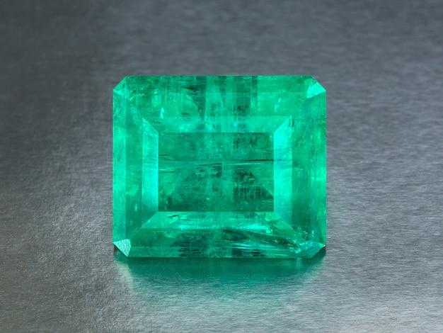 Grande smeraldo naturale su un fondo grigio, fine di percorso di ritaglio inclusa alto vicino.