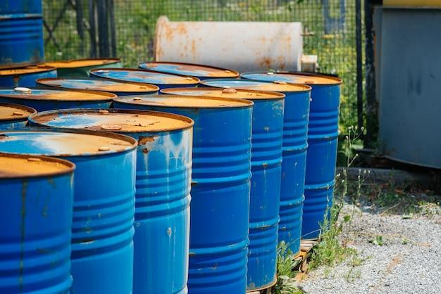 Grandi fusti di petrolio, blu. barili di prodotti chimici in un magazzino aperto. barili arrugginiti. barile per petrolio.