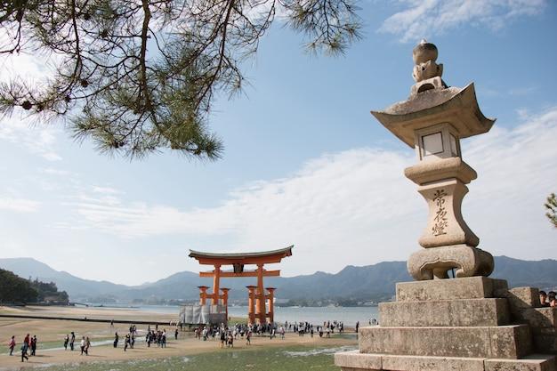 Grande pietra della pagoda sulla costa e sul portone di torii a miyajima a hiroshima, giappone