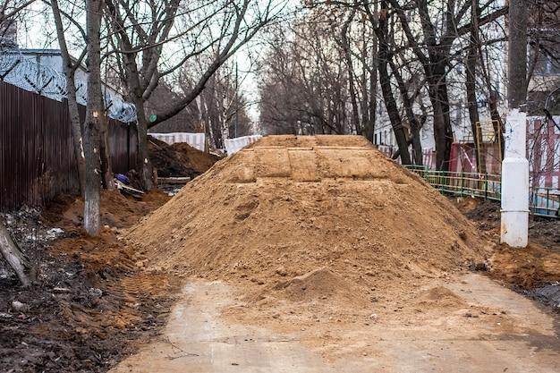 Grande mucchio di sabbia sul marciapiede passaggio allagato dei lavoratori i problemi non sono riparazioni stradali di alta qualità