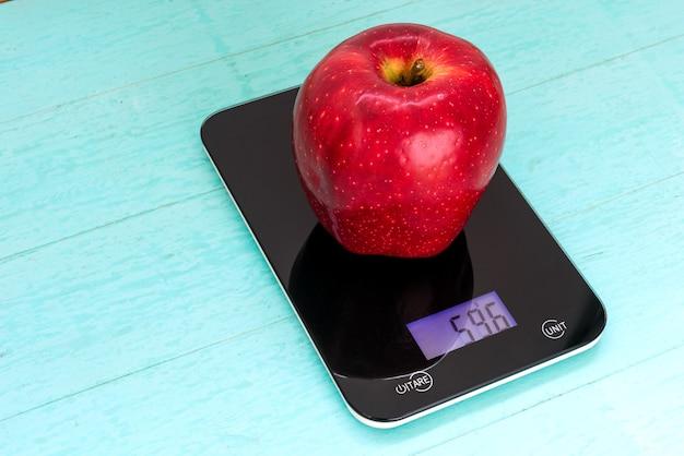 Grande mela rossa sulla bilancia