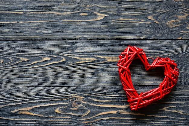 Grande cuore di rattan rosso su uno sfondo di legno scuro. avvicinamento. vista dall'alto. san valentino sullo sfondo.