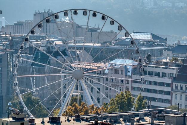 Grande attrazione rotonda della ruota panoramica, budapest eye su uno sfondo di vecchia parte storica della città di budapest, ungheria.