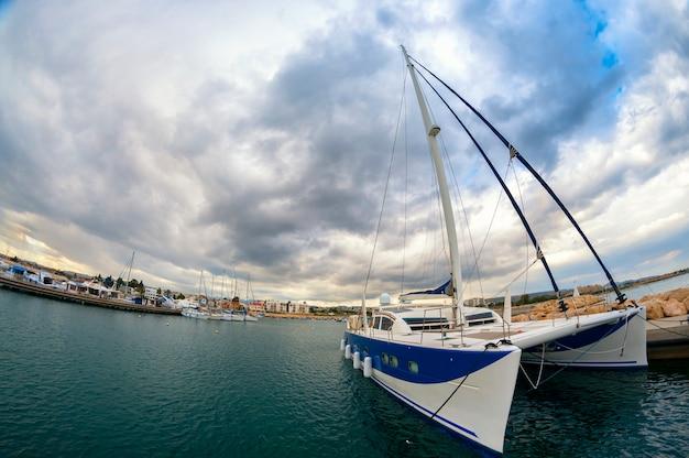 Grande catamarano a vela ormeggiato contro un cielo drammatico