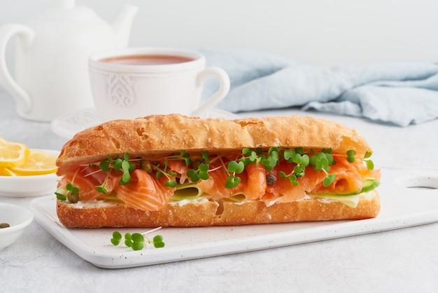 Grande panino con salmone, crema di formaggio e fette di cetriolo sul tavolo di cemento bianco