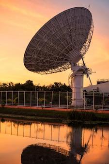 Grande piatto satelite al tramonto con riflesso d'acqua